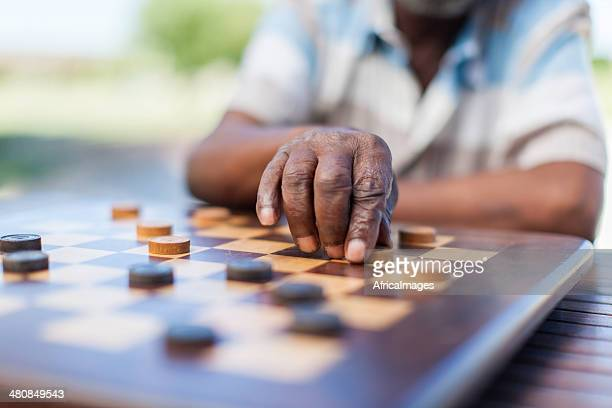 African senior playing chess, making a move