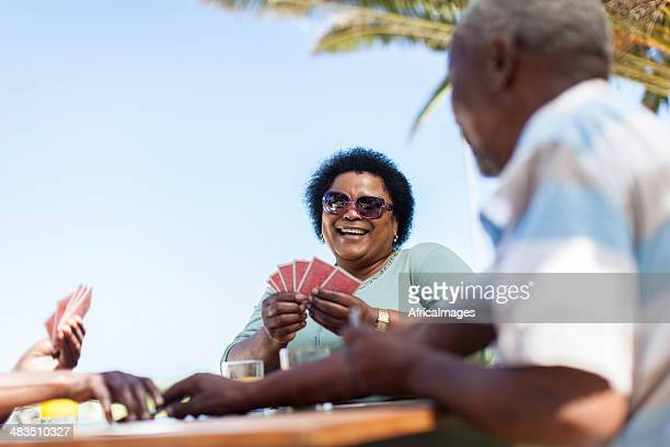 African senior women having a good laugh while playing cards