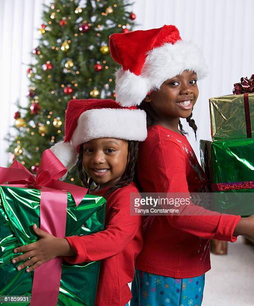 African sisters holding Christmas gifts