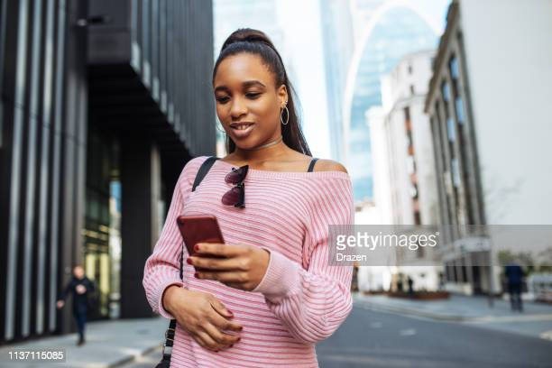 African student with backpack in Europe, using mobile phone