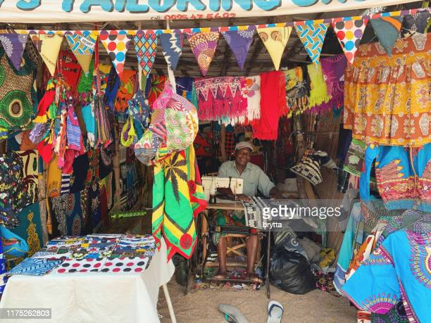 african tailor sewing chitenjes in  cape maclear in malawi - malawi stock pictures, royalty-free photos & images