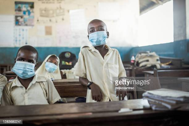 african  teacher and her students wearing protective face mask at the elementary school after covid-19 - africa stock pictures, royalty-free photos & images