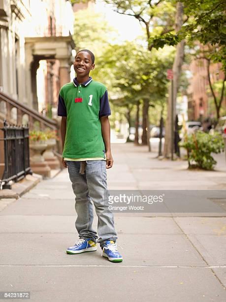 African teenage boy smiling in urban setting