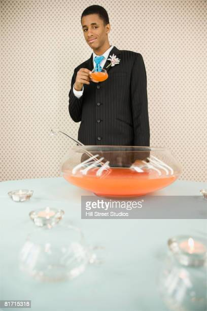 African teenaged boy in suit holding punch cup