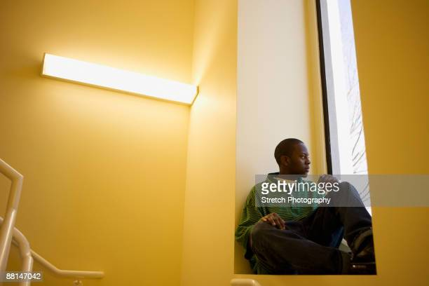 african teenager sitting in window sill - good; times bad times stock pictures, royalty-free photos & images