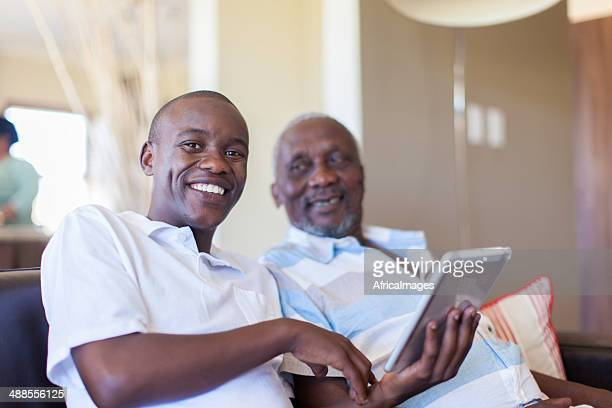 Adolescente africana sonriente sobre su grandfathers progreso con el comprimido.
