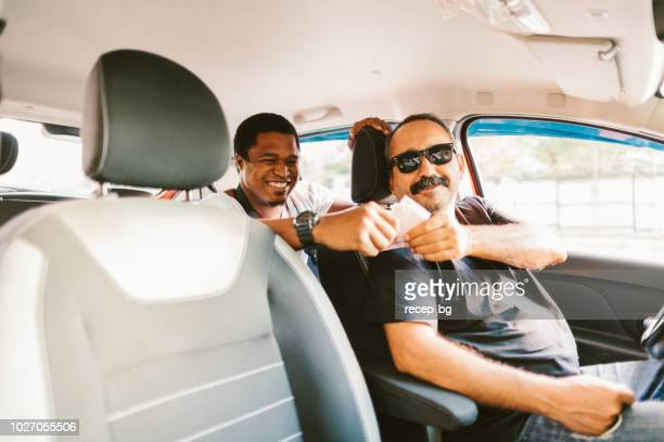 african tourist paying taxi fare - taxi driver stock photos and pictures