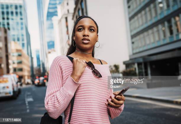 African tourist with backpack in Europe, using GPS device.
