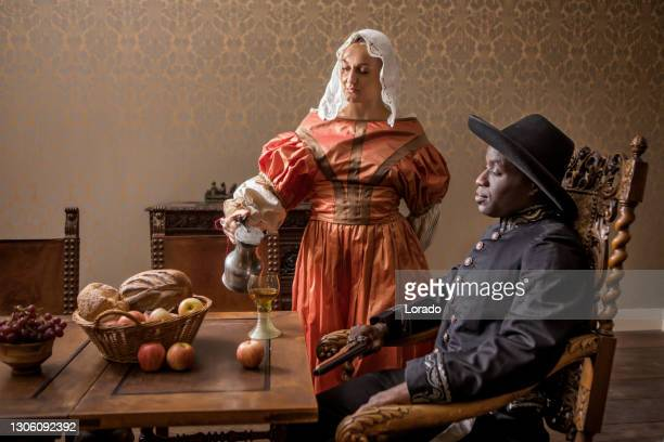 african traditionally dressed european man with a serving girl - black history in the uk stock pictures, royalty-free photos & images