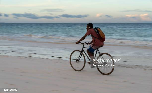 african traveler cycling on the diani beach, mombasa, kenya, africa. - mombasa stock pictures, royalty-free photos & images
