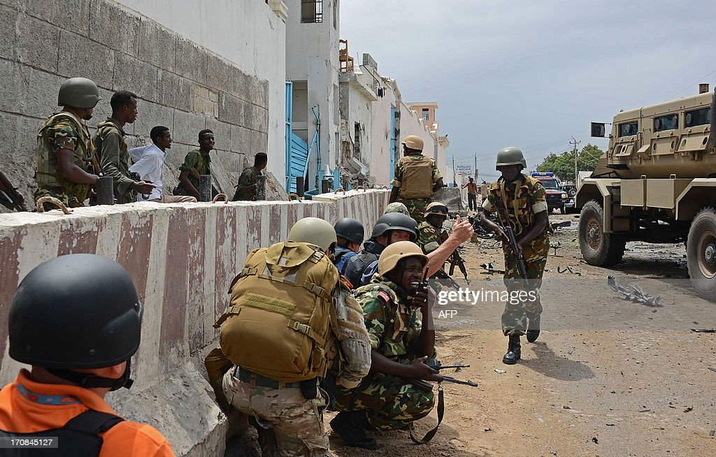 African Uinion force in Somalia (AMISOM) soldiers react on June 19, 2013 after Al-Qaeda linked Shebab insurgents shot and blasted their way into the United Nations (UN) compound in Mogadishu. Three foreigners and at least two Somali security guards were killed during the attack -- the most serious attack on the UN in the troubled country in recent years.