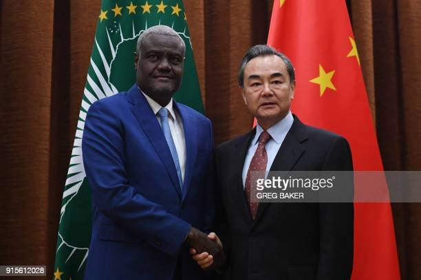African Union chief Moussa Faki Mahamat shakes hands with China's Foreign Minister Wang Yi before their meeting in Beijing on February 8 2018 Moussa...
