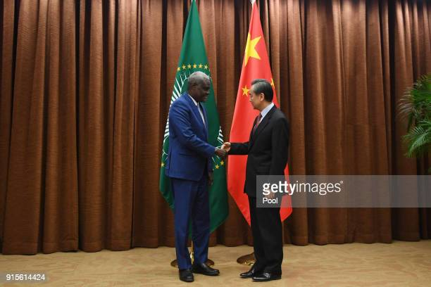 African Union Commission Chairperson Moussa Faki Mahamat shakes hands with Chinese Foreign Minister Wang Yi before a meeting on February 8 2018 in...
