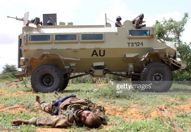 African Union soldiers on a tank drive past the body of an al-shebab fighter lying on the ground following fighting in Balad town, Middle Shabelle...