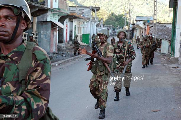 African Union troops from Tanzania and Comoran troops walk down a street in Anjouan on March 25 2008 Comoran forces and African Union troops launched...