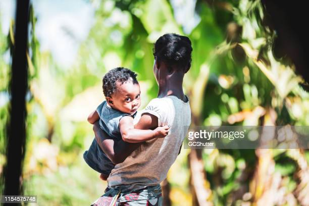 african village woman holding her baby in her arms - native african girls stock pictures, royalty-free photos & images