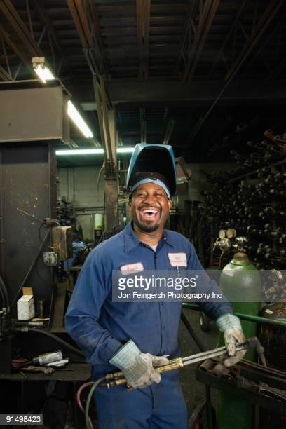 African welder working in repair shop
