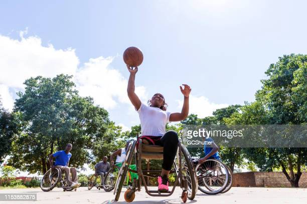 african wheelchair basketball players on the community ground playing a friendly match - taking a shot sport stock pictures, royalty-free photos & images
