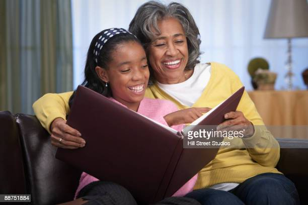african woman and granddaughter looking at photo album - childhood photo album stock photos and pictures