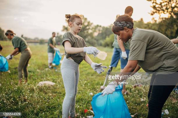 african woman and little girl collecting garbage together from the public park - south_agency stock pictures, royalty-free photos & images