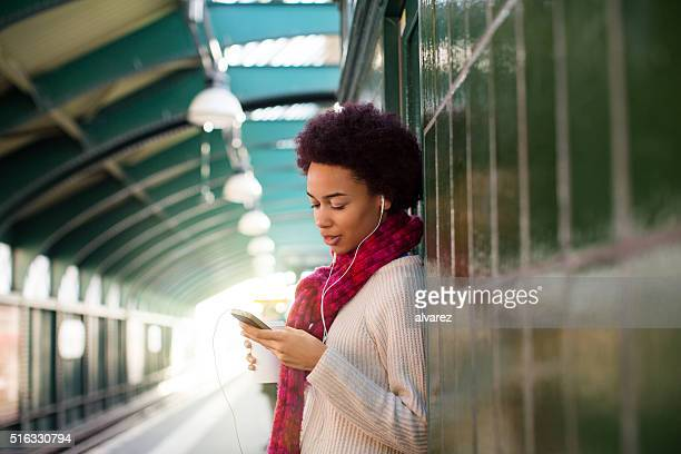 African woman at subway station waiting for the train