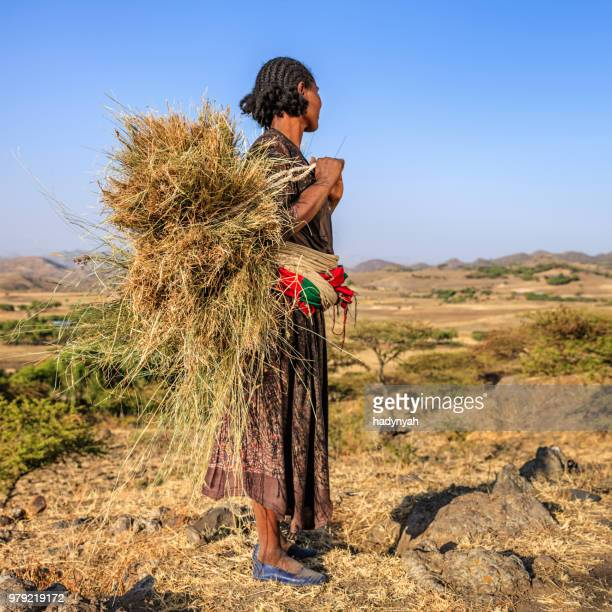 African woman carrying straw, East Africa