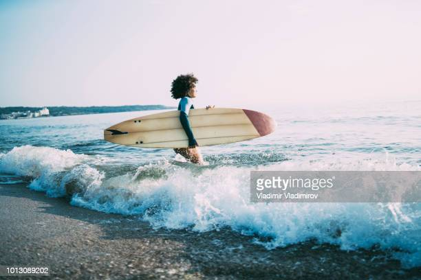 african woman carrying surfboard in sea - breaking wave stock pictures, royalty-free photos & images
