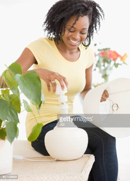 African woman changing light bulb