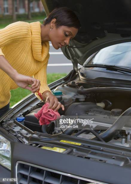 african woman checking oil in car engine - oil change stock pictures, royalty-free photos & images