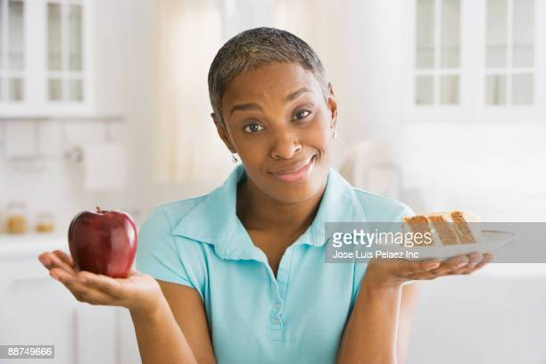african woman choosing snack - temptation stock pictures, royalty-free photos & images