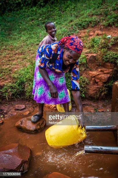 井戸から水を集めるアフリカの女性、ケニア、東アフリカ - 児童就労 ストックフォトと画像