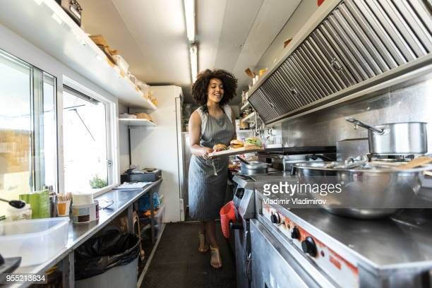 african woman cooking inside of food truck - market vendor stock pictures, royalty-free photos & images