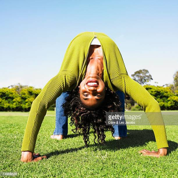 African woman doing back bend in grass