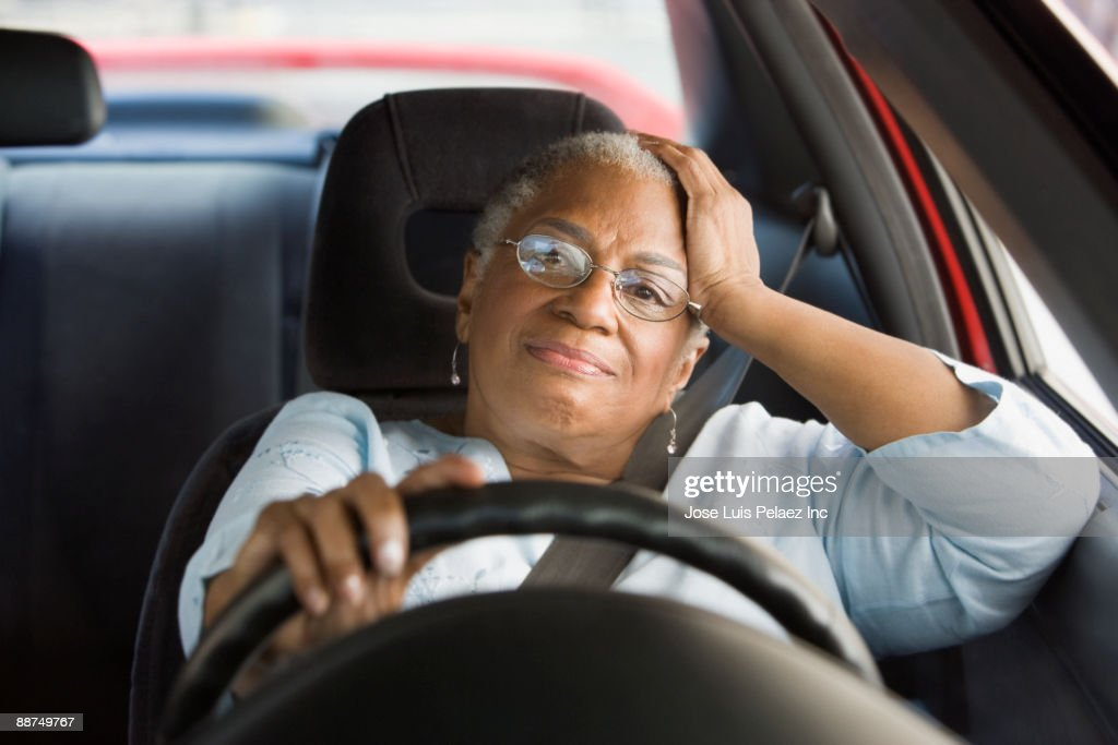 African woman driving car in traffic : Stock Photo