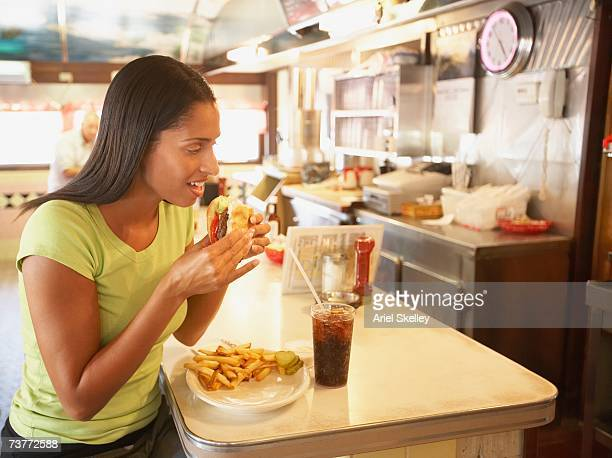 African woman eating at counter in diner