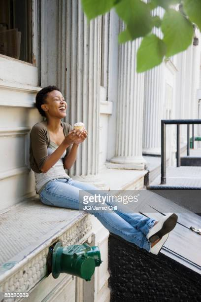 African woman eating cupcake outdoors