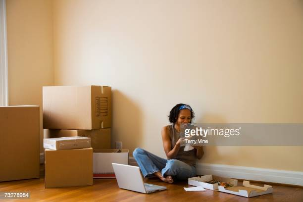 African woman eating pizza on floor next to moving boxes
