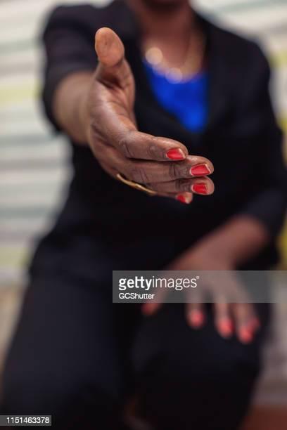 afrikaanse vrouw uitbreiding van arm tot gebaren handdruk - telefoonberoep stockfoto's en -beelden