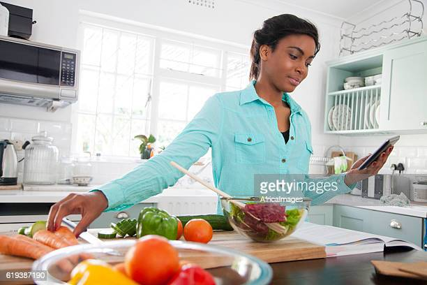 African woman following a recipes steps.
