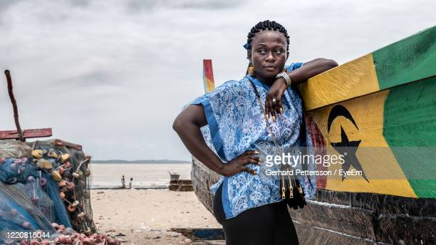 african woman from ghana with blue dress stands by a fishing boat on a beach in ghana west africa - ghana stock pictures, royalty-free photos & images