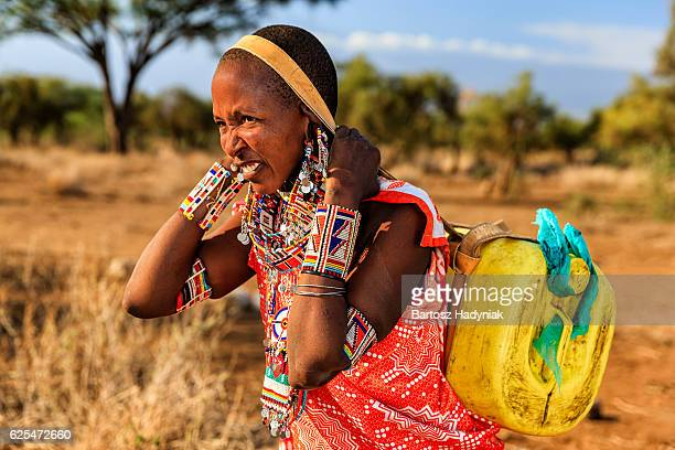 African woman from Maasai tribe carrying water, Kenya, East Africa