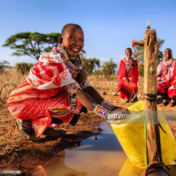 african woman from maasai tribe collecting water, kenya, east africa - east african tribe stock pictures, royalty-free photos & images