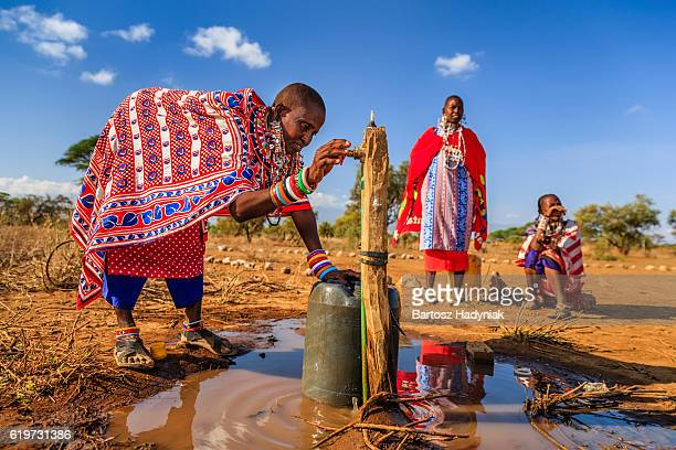 african woman from maasai tribe collecting water, kenya, east africa - masai fotografías e imágenes de stock