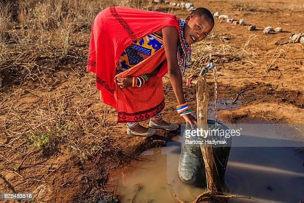 Femme d'Afrique de Maasai tribu collecte de l'eau, Kenya, Afrique de l'est
