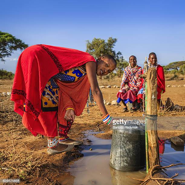 african woman from maasai tribe collecting water, kenya, east africa - east africa stock photos and pictures