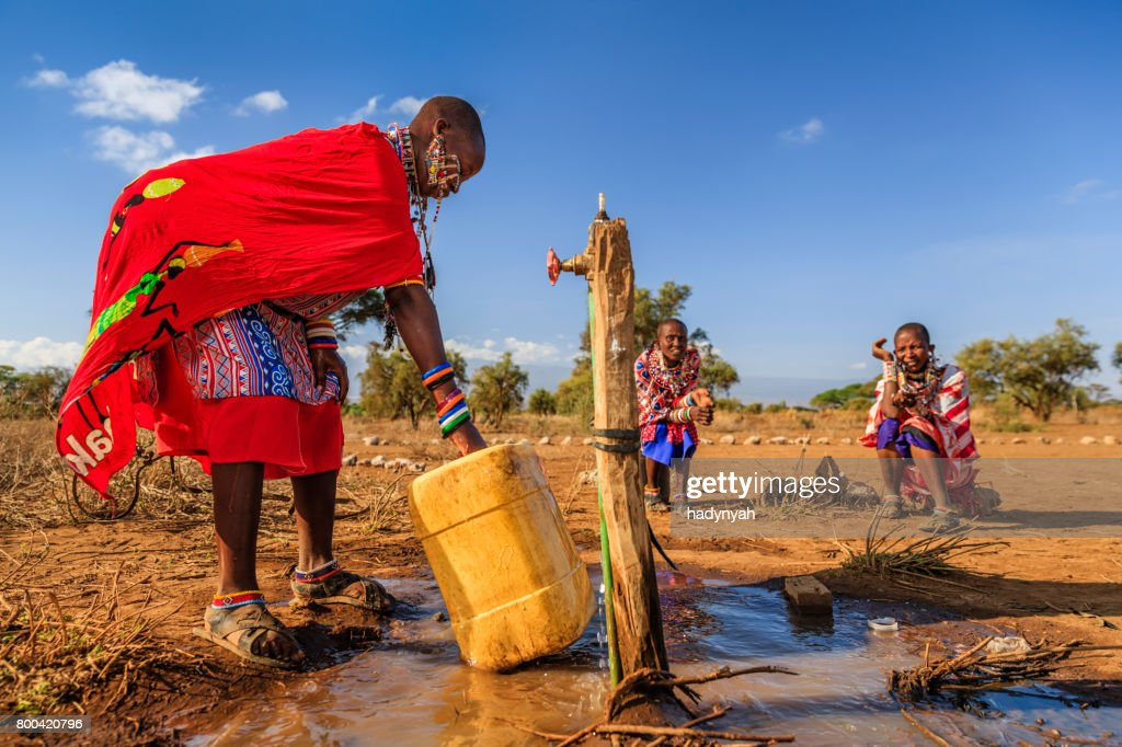 African woman from Maasai tribe collecting water, Kenya, East Africa : Stock Photo