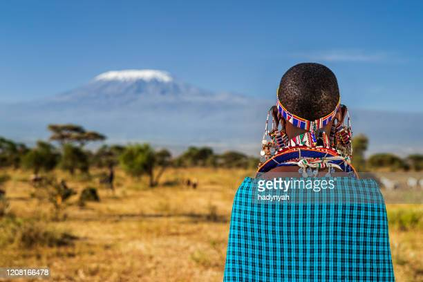 african woman from masai tribe looking at mount kilimanjaro, kenya, east africa - african tribal culture stock pictures, royalty-free photos & images