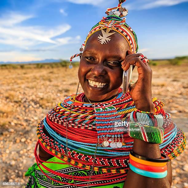 Mujer africana de tribu Samburu mediante teléfono móvil, Kenia, África