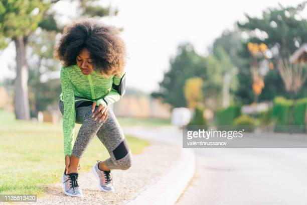 african woman got sport injured while jogging on the street - ankle stock pictures, royalty-free photos & images