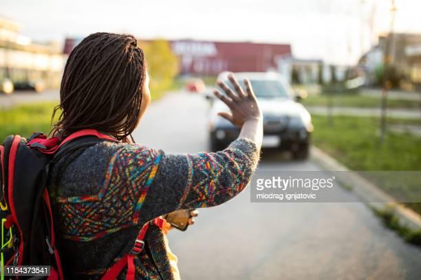 afrikaanse vrouw die aan taxi op de straat begroet - zwaaien gebaren stockfoto's en -beelden